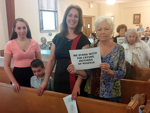 Three generations hold up sign