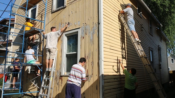 Nehemiah Mission Team painting and scraping house