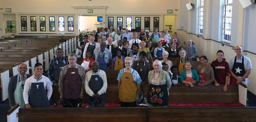 Church members stand in pews with aprons