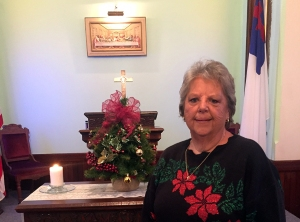 Carolyn Thompson holding Christmas tree in from of alter