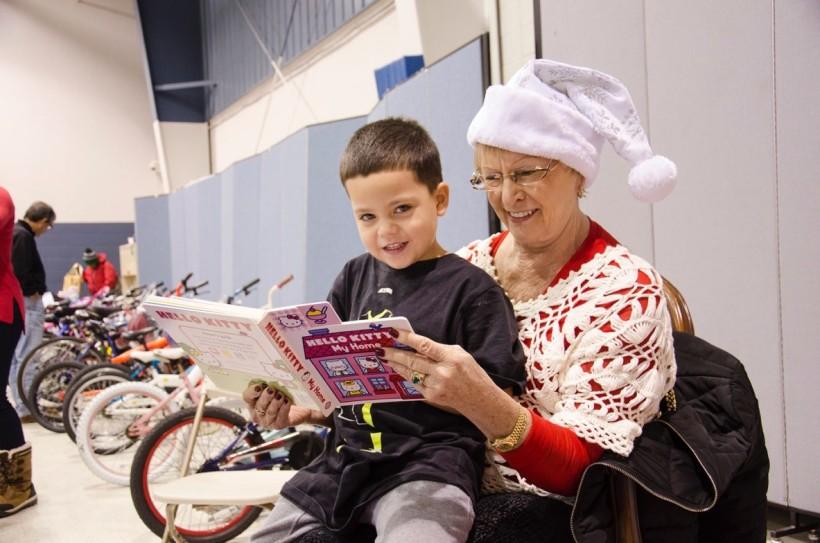 Child sitting on Santa helper's lap with book
