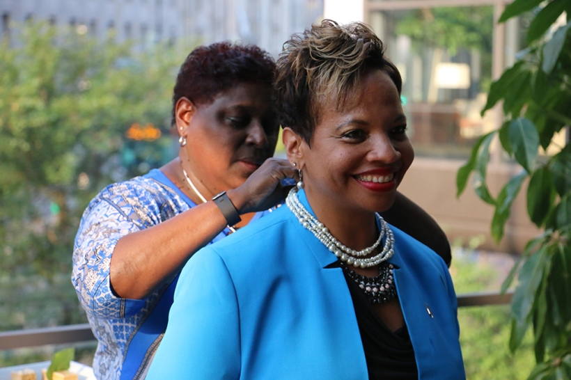 Bishop Tracy S. Malone receives a string of pearls from the Rev. Danita Anderson