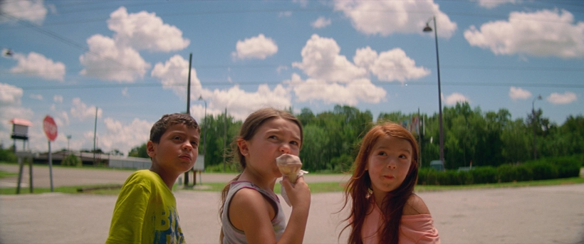 Two girls and a boy near a highway