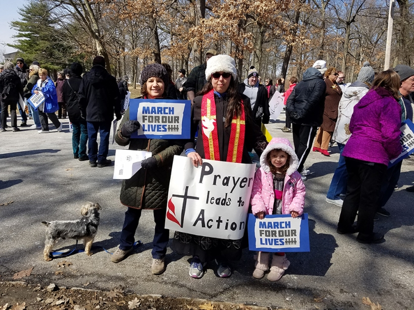 "Rev. Abby Auman with her daughter and friend with sign ""Prayer leads to action"" at the Youngstown rally."
