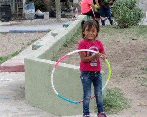 Young girl having fune with hoola-hoop in the park