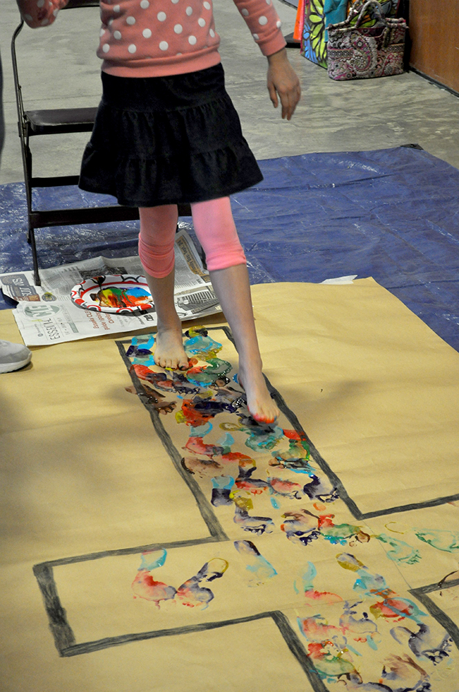 Young girl paints with her feet within the lines of a cross painted on paper