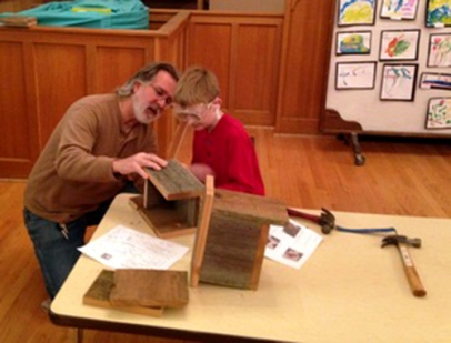 ADult and boy work on wood project together