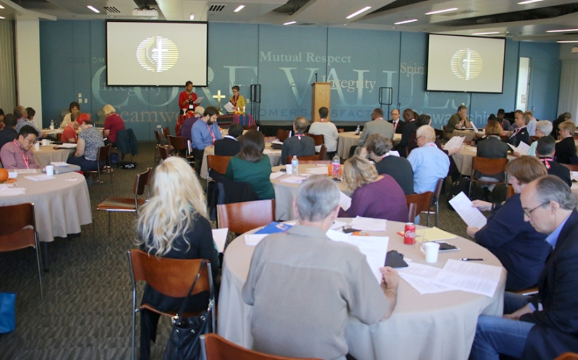 NCJ delgates gather at table, Bishop Malone at podium