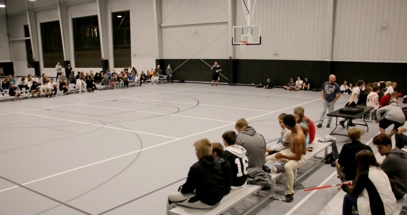 Clergy devotion, full view of gym, students sitting on bleachers