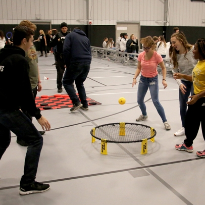 Teen girls and boys playing trampoline game with ball