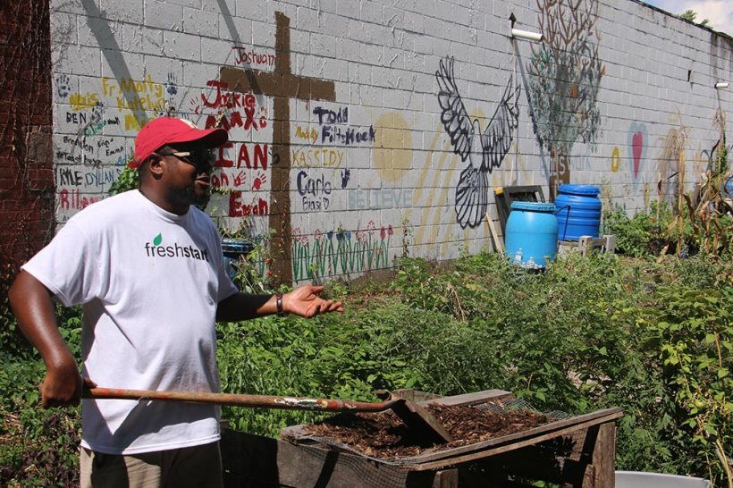 In front of building wall painted with cross and encouragement Justice Slappy speaking, while raking