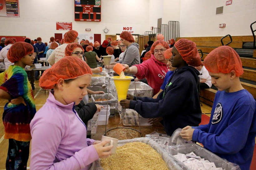 Youth in production line packing meals